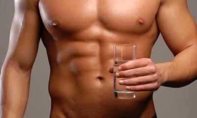 Hombre musculoso sujetando un vaso de agua.beber agua.