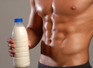 Hombre sano y musculoso sujetando una botella de leche.