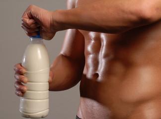 Hombre sano y musculoso destapando una botella de leche.