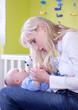 Attraktive blonde Frau mit Baby beim Nägel schneiden