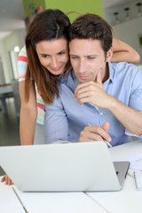 Couple at home sitting in front of laptop