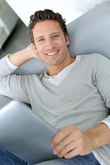 Smiling man looking at internet laying in sofa