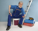 old master plasterer sitting on a bucket of paint