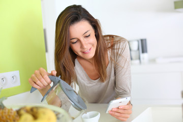 Young woman at home connected on smartphone