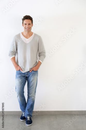 Handsome relaxed guy standing on white backgroud