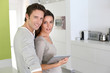 Cheerful couple looking at internet on tablet