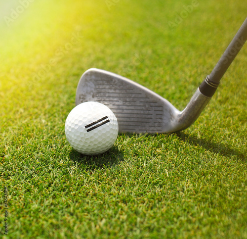 Golf player hitting the ball into the whole