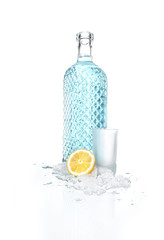 Bottle of vodka with small beaker glass and lemon