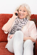 Attraktive Seniorin telefoniert auf dem Sofa