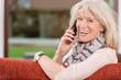 Glückliche Seniorin telefoniert auf dem Sofa