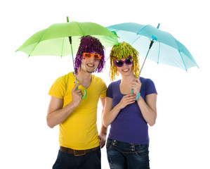 Funny couple with wigs, sunglasses and umbrellas