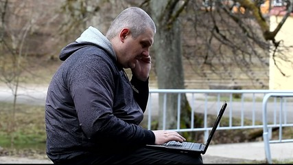 Man with cell phone and  PC at outdoor