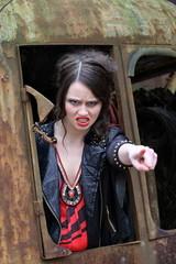 Wütende junge Frau  im Fenster eines alten Baggers