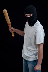 Masked man preparing to attack with bat
