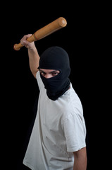 Masked man aims and attack with bat