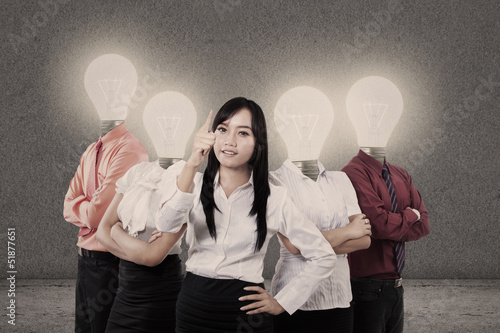 Businesswoman and team with light bulb heads