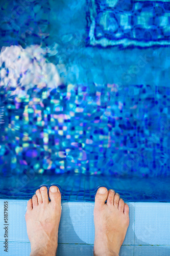 feet on the edge of the pool