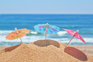 Small beach umbrellas on a beach on a background of the sea.