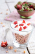 Muesli with cream and strawberry on wooden table