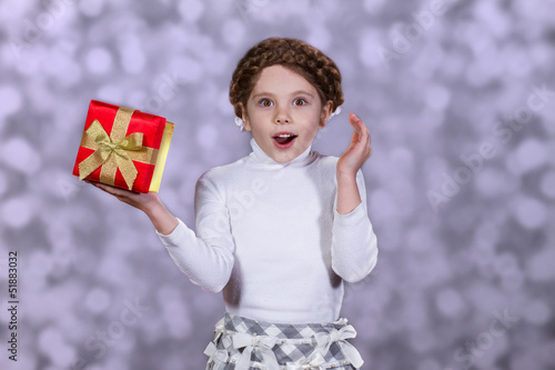 Surprised little girl with gift in her hand
