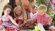 Parents And Children Enjoying Chocolate Cake At Party