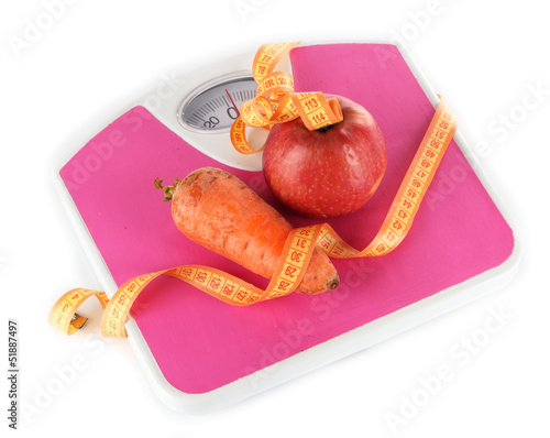 Apple and carrot on scales isolated on white
