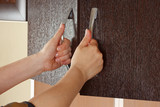 Fototapety Women's hands are open the cupboard doors, dark wood