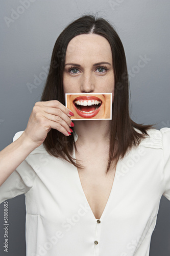 woman covering image with big smile