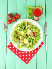 Caesar salad on blue plate, on color wooden background