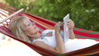 Senior Woman In Hammock Using Tablet Computer