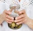 Senior woman hands holding jar with coins closeup. isolated