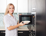Fototapety Woman warms up food in the microwave