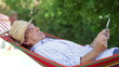 Senior Man In Hammock Using Tablet Computer