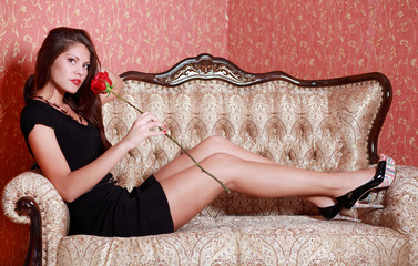 Beautiful girl in black dress holds red rose, sits on couch