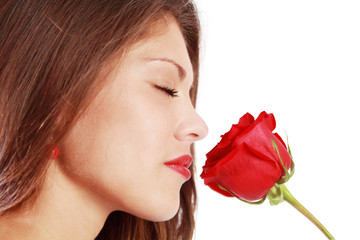 Close up of woman sniffing red rose with closed eyes