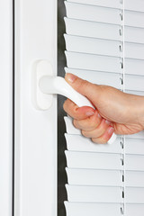 Hand opens the white plastic the window with shutters