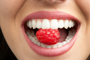 Perfect teeth biting raspberry.