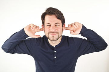 young man covering ears from loud noise, isolated on white backg