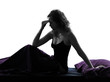 woman headache hagover sitting on bed silhouette