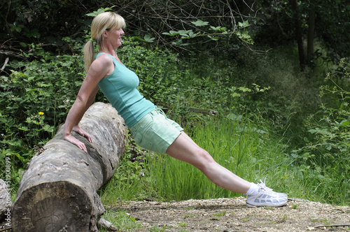 Woman keeping fit outdoors push ups using a log