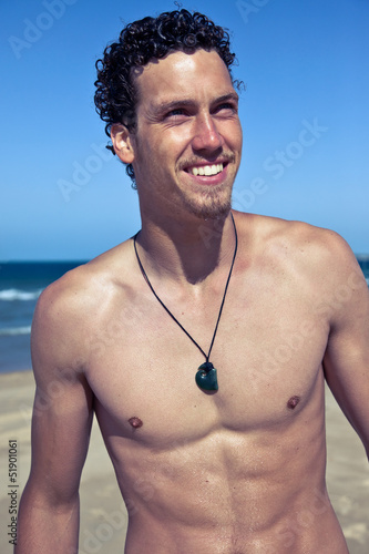 Fashion portrait of a young fit man on the beach