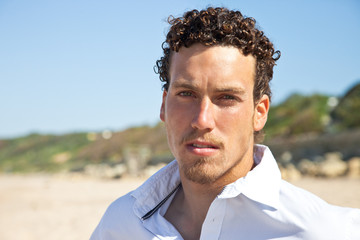 Handsome mediterranean young man with curly hair on the beach