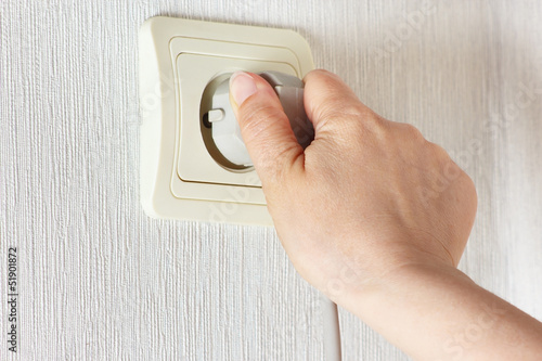 Hand inserting a plug in the socket on the wall