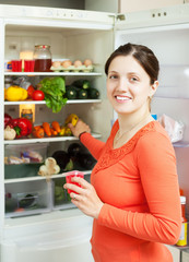 Happy woman looking for something in fridge