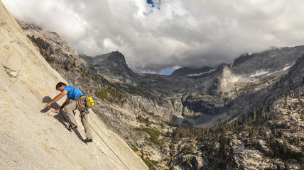 Climber scales a cliff.