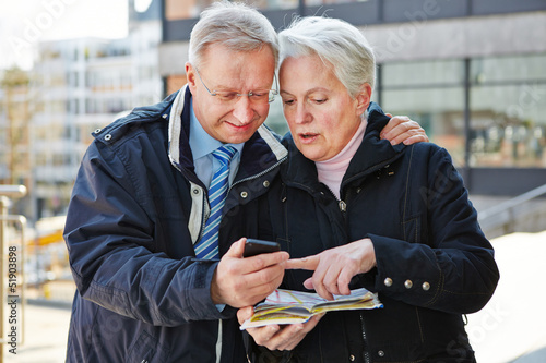Senior couple as tourists with map