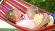 Two Boys Relaxing In Garden Hammock Together