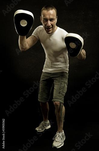 Sportlicher junger Mann mit Pratzen in Abwehrhaltung
