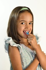 Little Hispanic Girl Flossing her Teeth