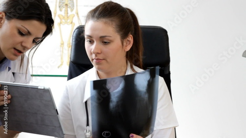 Consultation X-ray results with tablet in office - tracking shot